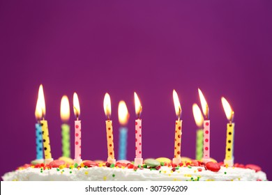 Birthday cake with candles on purple background