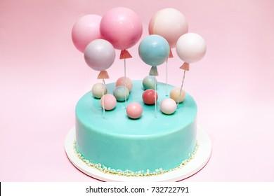 Birthday cake. Chocolate balls and balloons decor. Pink background.
