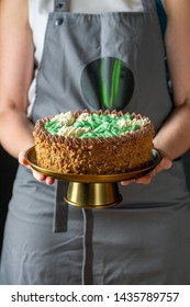 Birthday cake with chocolate cream on a bronze stand in women's hands on a dark background, selective focus.