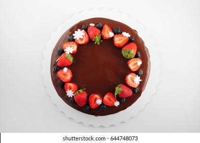 Birthday cake in chocolate with strawberries, blueberries and snowflake on white background. Top view. Picture for a menu or a confectionery catalog.