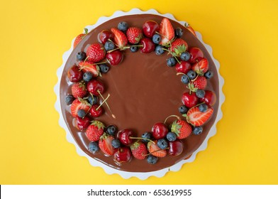 Birthday cake in chocolate with strawberries, blueberries and cherry on yellow background. Top view. Picture for a menu or a confectionery catalog.