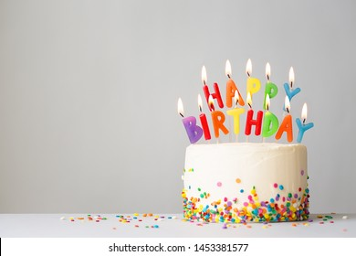 Birthday cake with colorful candles spelling happy birthday