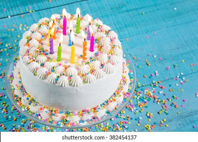 Birthday cake with colorful sprinkles and Candles over blue background