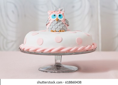 Birthday cake covered with fondant displayed on the pink cloth and glass tray; decorated with pink dots and an grey and pink fondant owl with blue eyes sitting on top