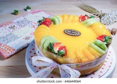 Birthday cake covered with fresh strawberry,kiwi,orange; Sponge cake with orange cream on top