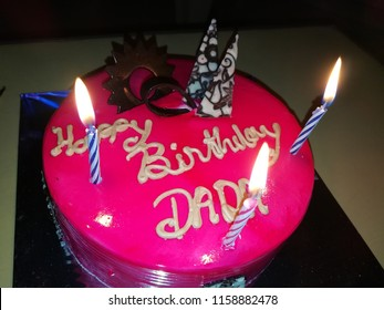 Birthday cake dada. Pink cake with candles. Chocolate decoration.