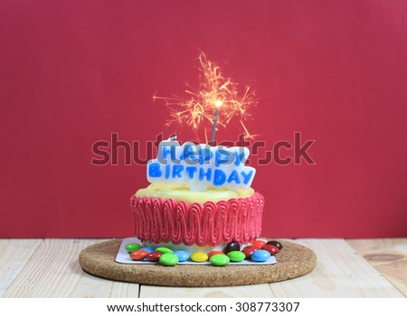 Birthday Cake Decorated With A Sparkler On Red Background