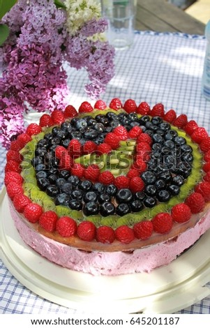Birthday Cake With Fruit Decoration In Front Of Lilac Flowers Heart On A