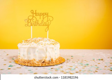 Birthday cake with golden topper. Birthday party celebration concept. Horizontal, bold yellow background