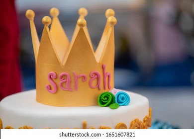 A birthday cake has the name Sarah written on it