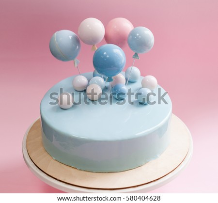 Birthday Cake With Light Blue Mirror Glaze Chocolate Balls And Balloons Decor Pink Background