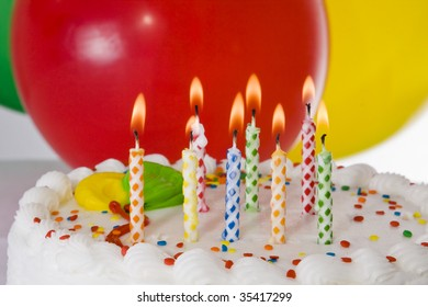Birthday cake with lighted candles and balloons.