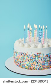 Birthday cake with lighting candles on blue background