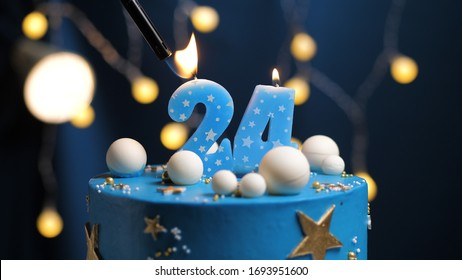 Birthday cake number 24 stars sky and moon concept, blue candle is fire by lighter. Copyspace on right side of screen. Close-up view