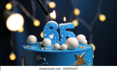 Birthday cake number 65 stars sky and moon concept, blue candle is fire by lighter. Copyspace on right side of screen. Close-up view