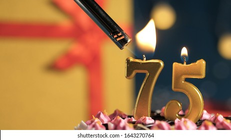 Birthday cake number 75 golden candles burning by lighter, background gift yellow box tied up with red ribbon. Close-up view