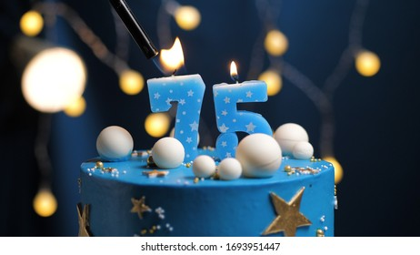 Birthday cake number 75 stars sky and moon concept, blue candle is fire by lighter. Copyspace on right side of screen. Close-up view