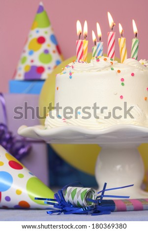 Birthday Cake On Pedestal With Multiple Lit Colorful Candles And Part Hats In Pink Background