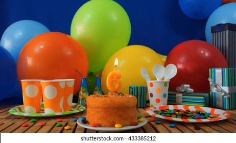 Birthday cake on rustic wooden table with background of colorful balloons, gifts, plastic cups and plastic plate with candies and blue wall in the background