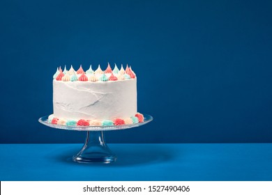 Birthday cake with pastel icing, c over a blue background.