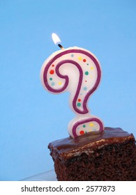 birthday cake with a question mark candle lit on top