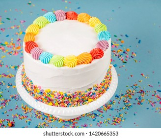 Birthday cake with rainbow icing and colorful Sprinkles over a blue background.