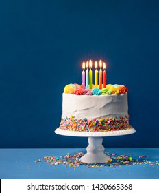 Birthday cake with rainbow icing, colorful Sprinkles and lit candles over a blue background.