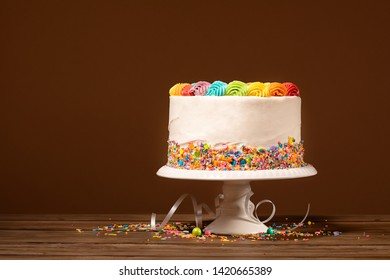 Birthday cake with rainbow icing and colorful sprinkles against a brown background.