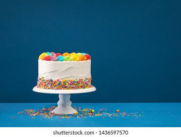 Birthday cake with rainbow icing, colorful Sprinkles over a blue background.