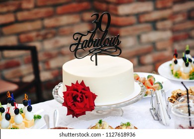 Birthday cake with red rose. Fabulous 30. Special cake 30 years old. Sweet table on birhday party outdoor. White round cake with flower.