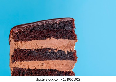 Birthday cake slice with chocolate filling. Close-up of chocolate layered cake with buttercream icing. Macro with chocolate frosting birthday cake