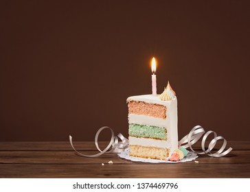 Birthday cake slice with three pastel colored layers and lit candle on a brown background