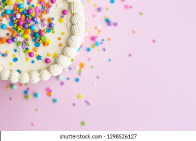 Birthday cake with sprinkles on a pink background