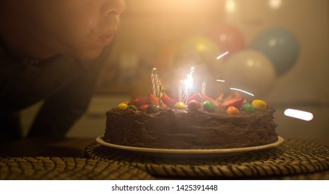 Birthday cake with strawberries and multicolored candies. A man blows out the candles on a birthday cake. Background with colorful balloons
