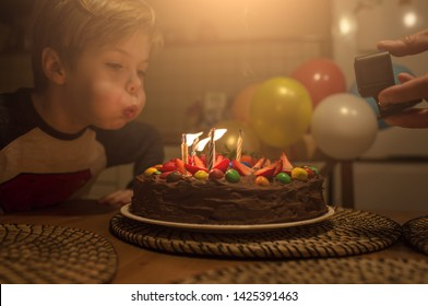 Birthday cake with strawberries and multicolored candies. Dad shoots video as his son blows out the candles. Background with colorful balloons and puffs of smoke