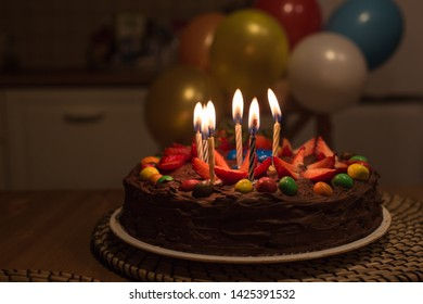 Birthday cake with strawberries and multicolored candies. Burning candles on the cake. Background with colorful balloons