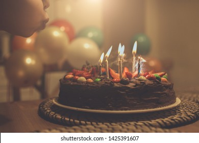 Birthday cake with strawberries and multicolored candies. A little boy blows out the candles on a birthday cake. Background with colorful balloons