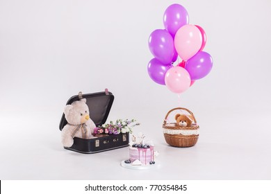 Birthday cake, teddy bear in vintage suitecase and balloons isolated on white background