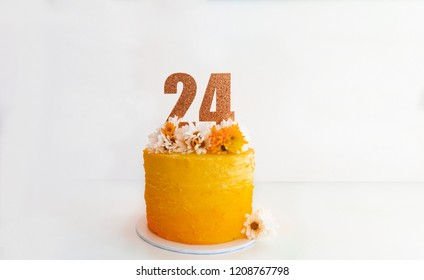 Birthday Cakes with the number 24 topper. Orange and yellow icing with white and orange flowers on top.