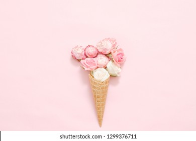 Birthday celebration concept. Assorted rose heads in cream cone on pink background.