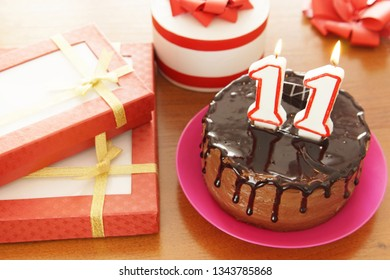 Birthday celebration at eleven years. A cake with burning candles in the form of numbers and a lot of gifts on a table
