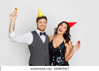 birthday, celebration and holidays concept - happy couple with party blowers and caps having fun