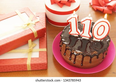 Birthday celebration at one hundred and ten years. A cake with burning candles in the form of numbers and a lot of gifts on a table
