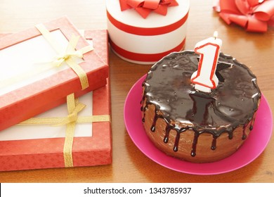 Birthday celebration at one year. A cake with burning candle in the form of number and a lot of gifts on a table