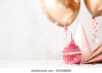 Birthday celebration with pink birthday cupcake, party hats and rose gold balloons