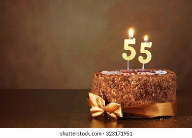 Birthday chocolate cake with burning candles as a number fifty five on brown background