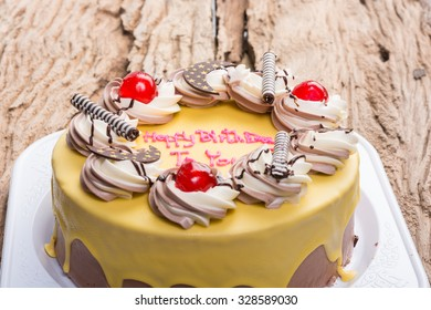 birthday chocolate cake topped with banana on wooden table