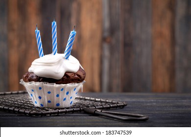 birthday chocolate muffin with three candles on rustic background