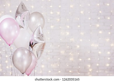 birthday and christmas concept - close up of colorful air balloons over brick wall background with lights
