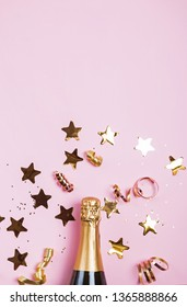Birthday or Christmas party decor on pink baqckground. Golden bibbons, confetti and glitter